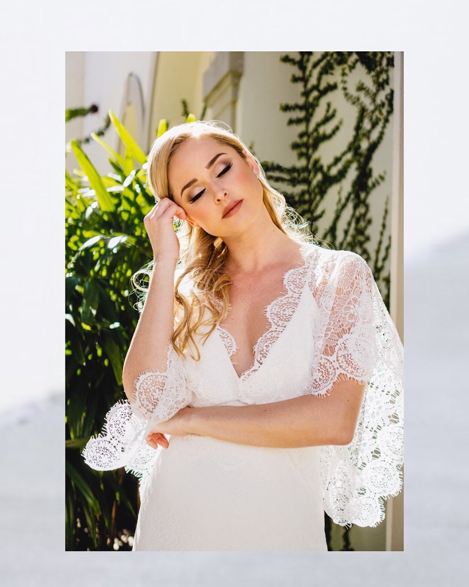 A beautiful bride poses wearing a handsewn lace wedding dress from sustainable wedding dress vendor Krustallos Couture
