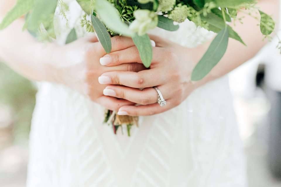 A bride holds her bouquet in an image that showcases her ethically sourced engagement rings.