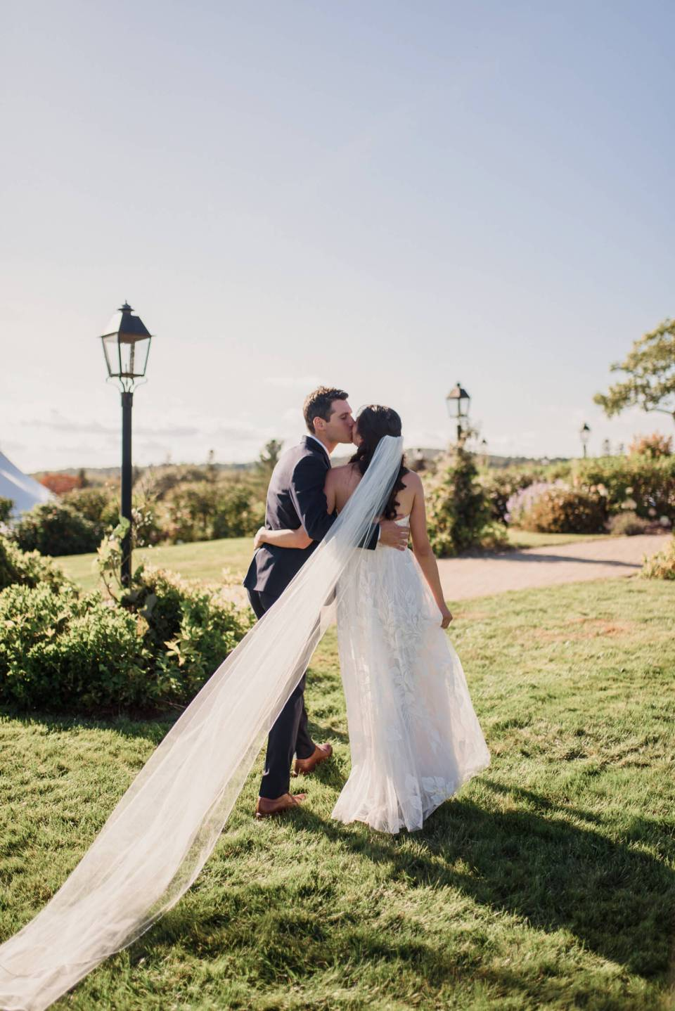 The happy couple kisses on their wedding day with the bride's long train trailing behind.