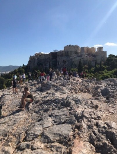 This is on the rocky surface of Areopagus with a view of the Acropolis in the background. St Paul probably would have stood at the end closest to the Acropolis facing the camera.