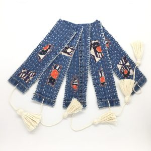 Textile bookmarks with hand embroidered details and visible mending, with tassel