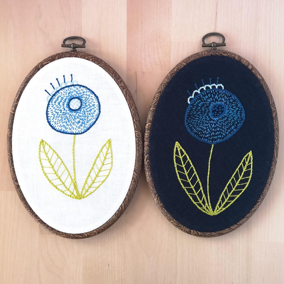 2 hoops with hand embroidered blue flower on different fabrics, white and navy blue