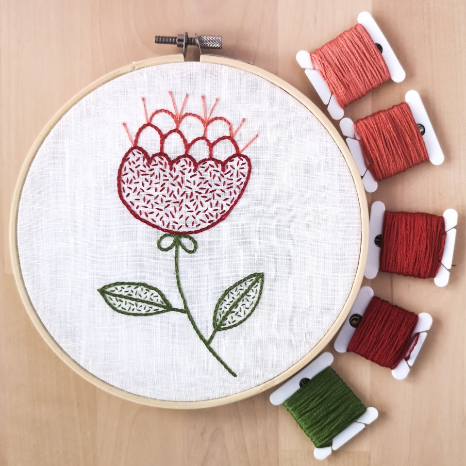 Hand embroidered Red flower on white linen with thread bobbins