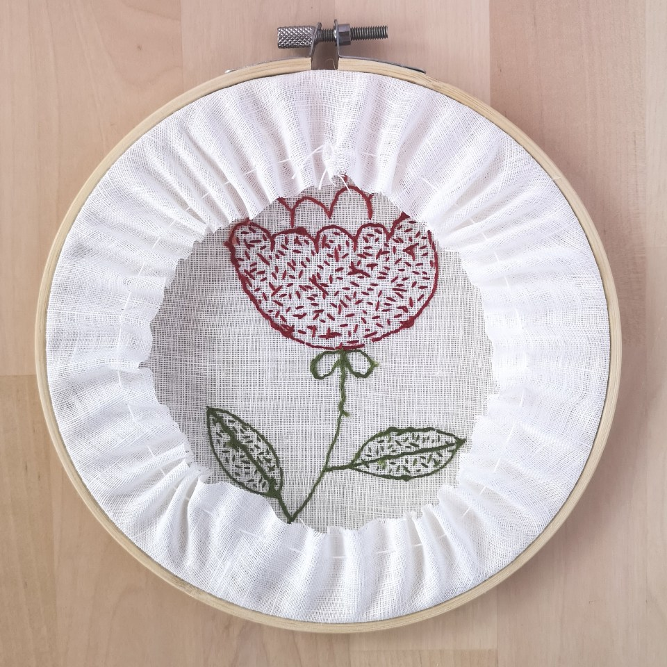 Red flower embroidery framing in a hoop