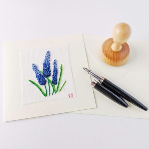 Hand embroidered postcard with grape hyacinth