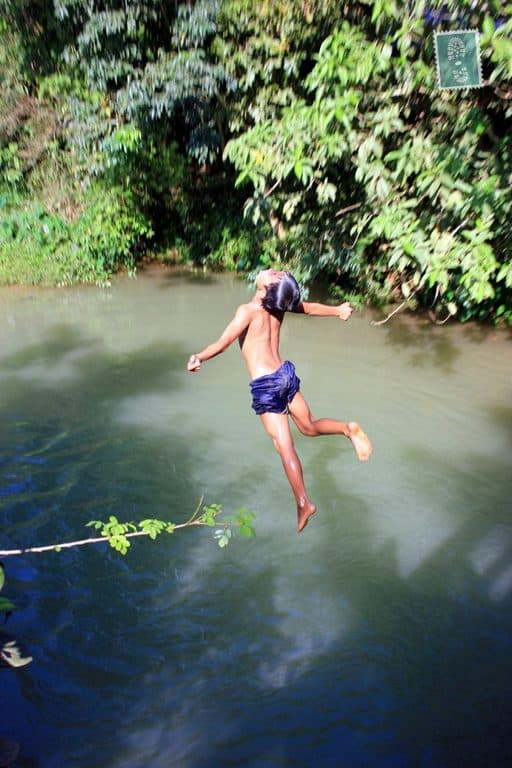 Laotian kid jumps in the river from the bridge
