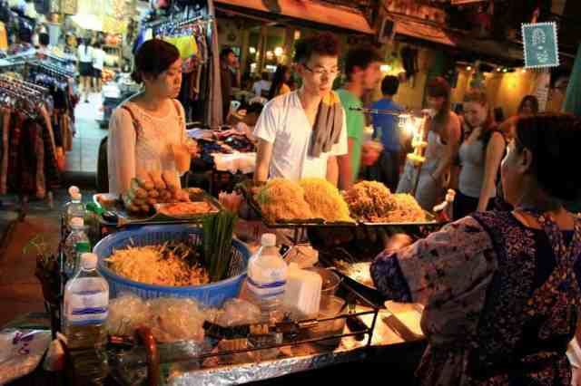 Khao San road, Thailand, two people are buying Pad Thai at night