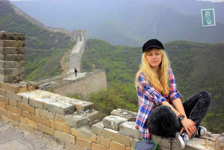 A girl is sitting at the Great Wall of China