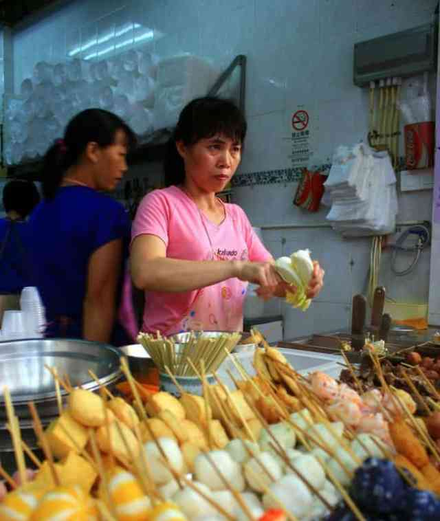 A local woman is serving food in Macau
