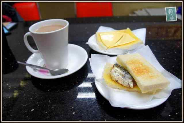 A mug of hot chocolate, ham fried egg and fish sandwich, cheese toast