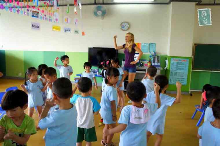 A foreign teacher is dancing with Chinese students