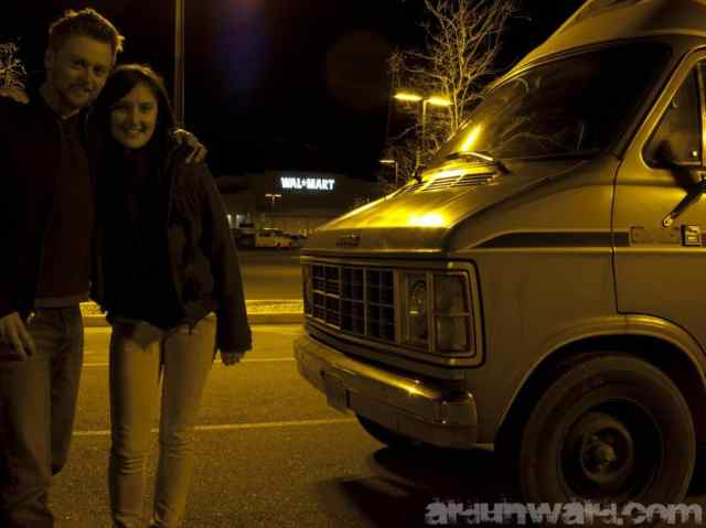 A guy and a girl are standing next to a car