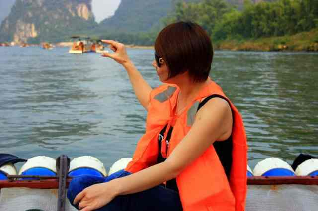A chinese girl is trying to catch a boat in Yangshuo