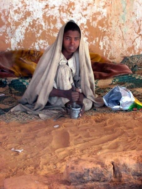 child grinding coffee in sudan