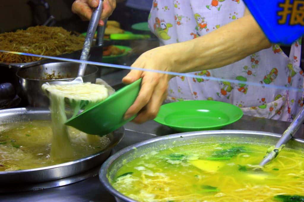 Local lady pouring in some noodle soup in Singapore