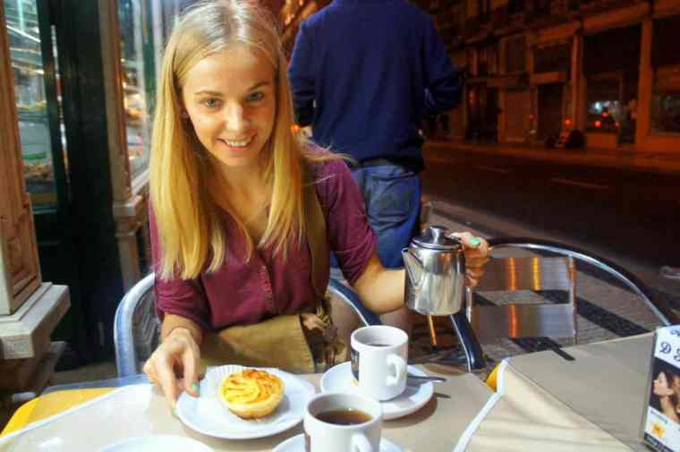 A girl is eating cake and drinking tea in Lisbon