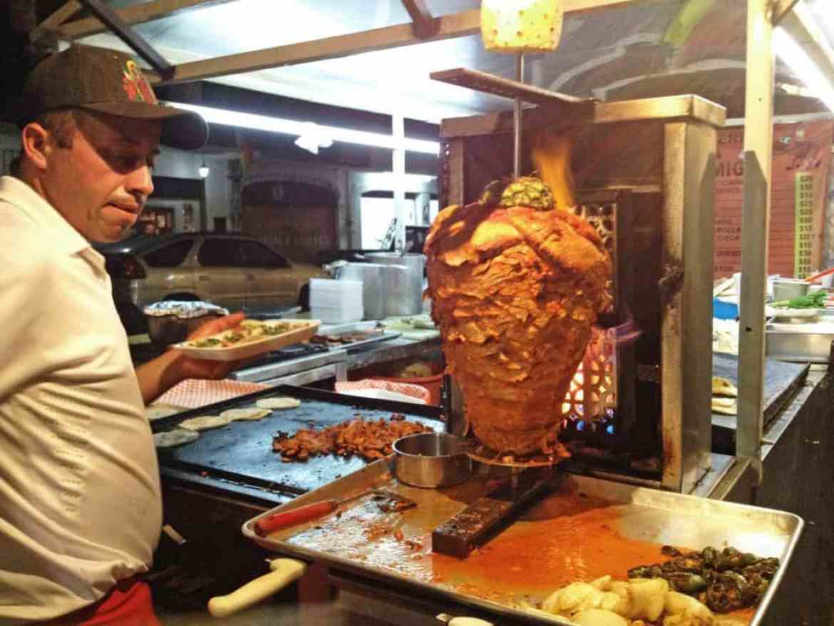 Al Pastor cooking on a spit at a food stand