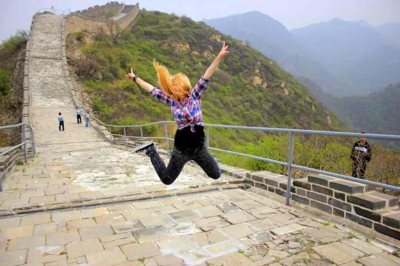 girl jumping at the Great Wall of China