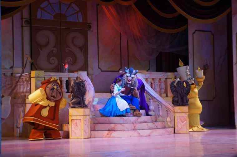 Beauty and the Beast sitting in front of a house in the musical on stage.