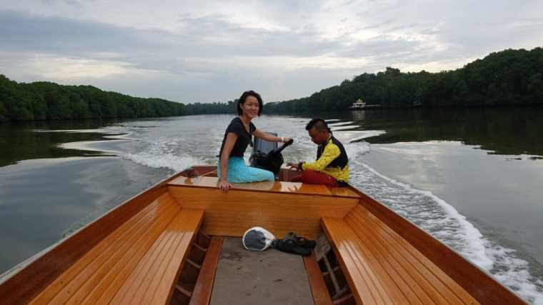 Lydia pilots a boat through Brunei mangroves