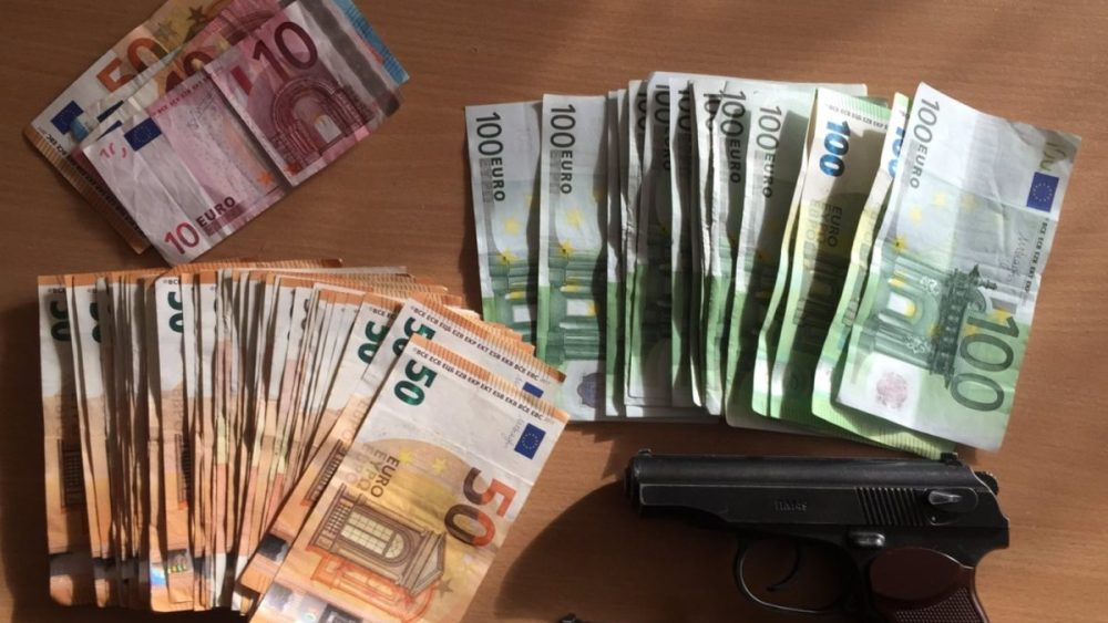 Cash and a firearm seized during raids on the human trafficking organisation in Lithuania