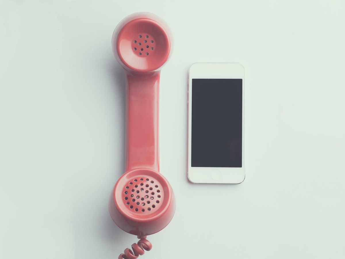 flat lay photography of red anti radiation handset telephone beside iphone