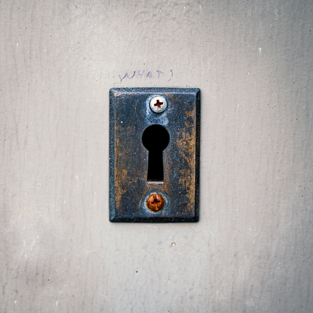 rusty keyhole with screws on concrete wall