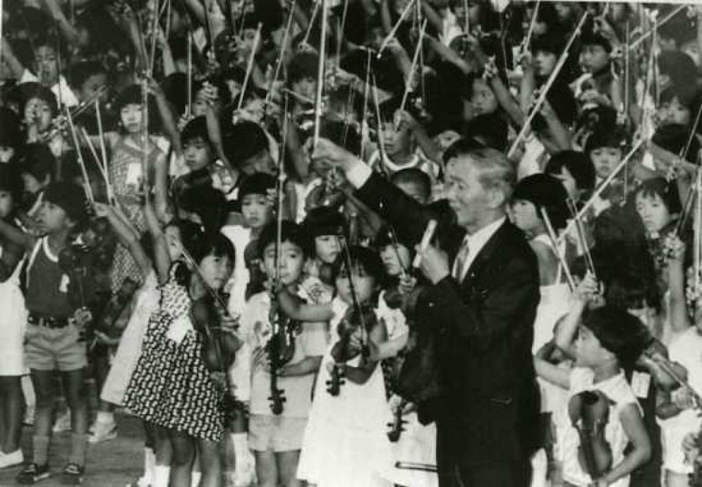 Dr. Shinichi Suzuki, founder of the Suzuki Method, with dozens of children playing violin