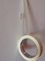 Pega la cinta de papel de arriba a abajo siguiente la guía del hilo. Puede ayudarte pegar en un par de sitios el hilo a la pared para que no se mueva.
