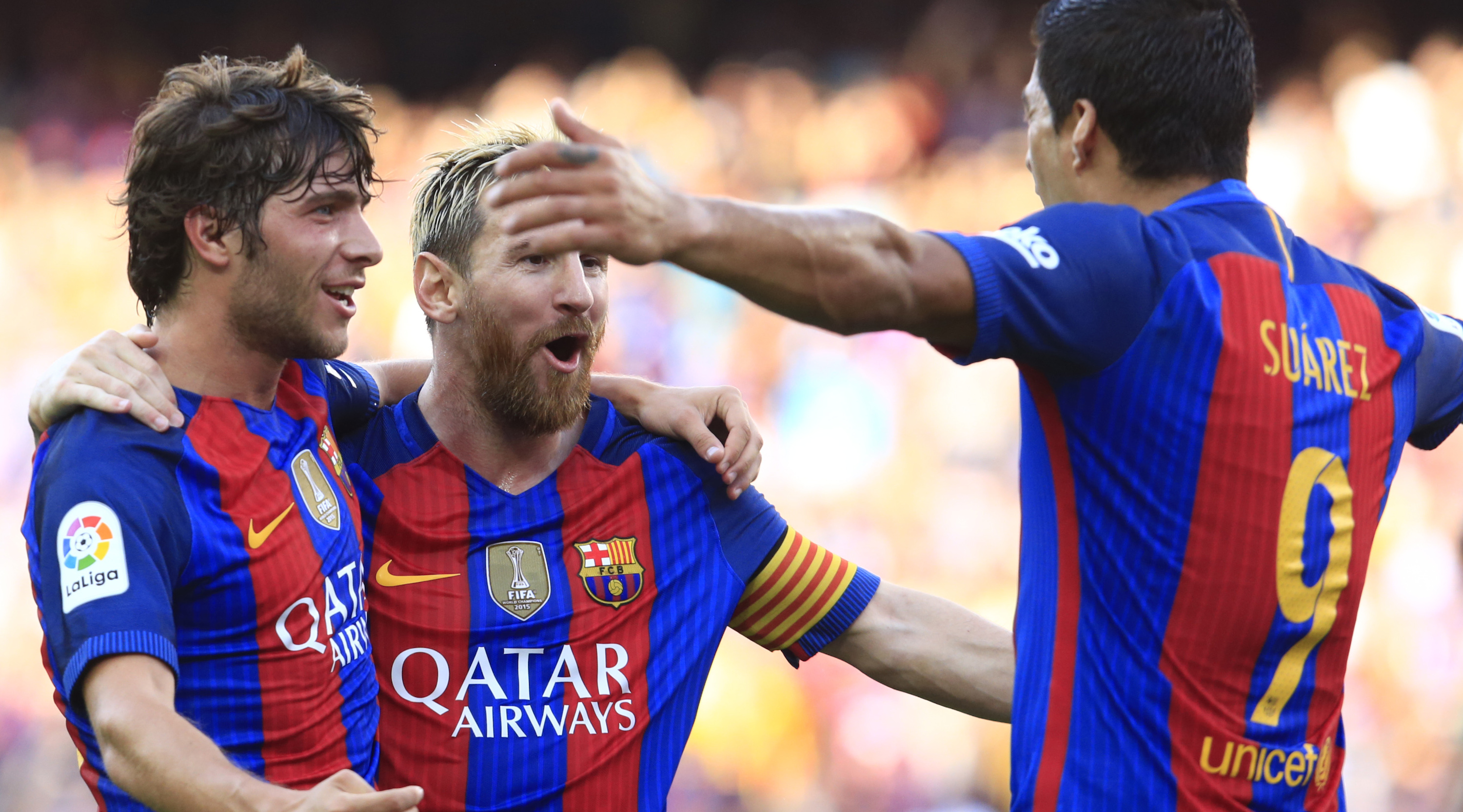 Barcelona's Argentinian forward Lionel Messi (C) celebrates after scoring with Barcelona's midfielder Sergi Roberto (L) and Barcelona's Uruguayan forward Luis Suarez during the Spanish league football match FC Barcelona vs Real Betis Balompie at the Camp Nou stadium in Barcelona on August 20, 2016. / AFP / PAU BARRENA (Photo credit should read PAU BARRENA/AFP/Getty Images)