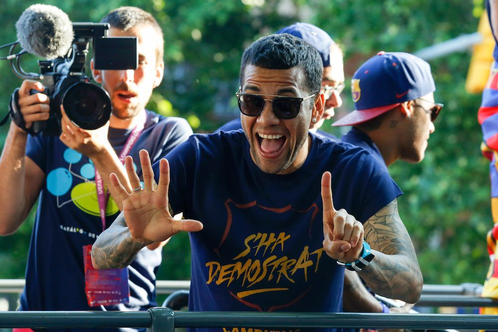TOPSHOT - Barcelona's Brazilian defender Dani Alves parades on a bus through the streets of Barcelona with te rest of his teammates to celebrate their 24th La Liga title, in Barcelona, on May 15, 2016