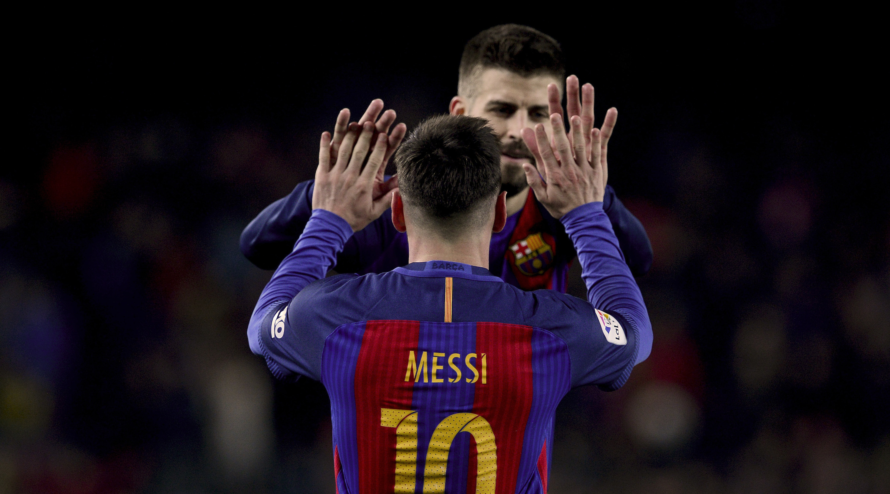 Barcelona's Argentinian forward Lionel Messi (L) celebrates a goal with teammate defender Gerard Pique during the Spanish league football match FC Barcelona vs RCD Espanyol at the Camp Nou stadium in Barcelona on December 18, 2016. / AFP / JOSEP LAGO (Photo credit should read JOSEP LAGO/AFP/Getty Images)