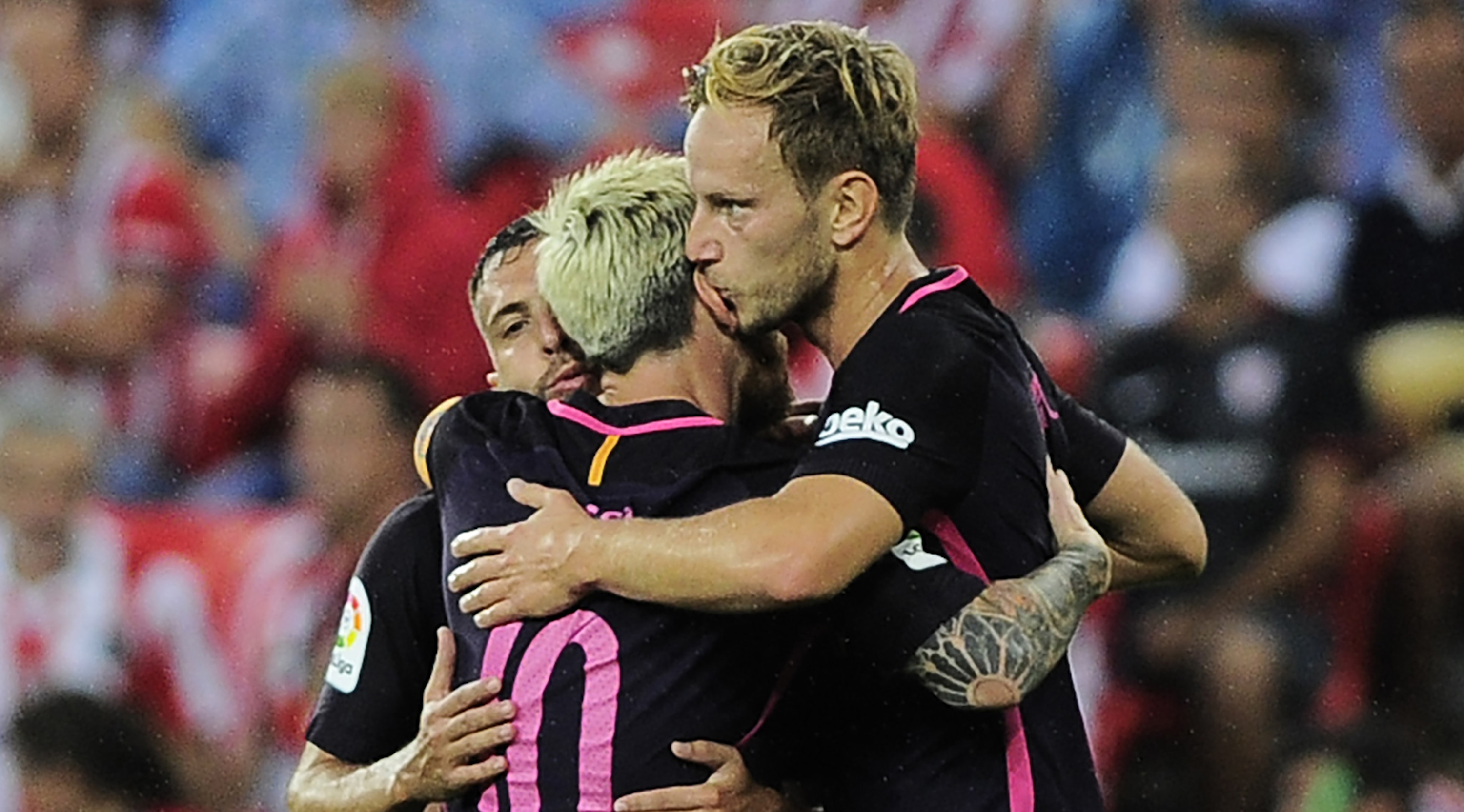 Barcelona's Croatian midfielder Ivan Rakitic (R) is congratulated by teammates defender Jordi Alba (L) and Argentinian forward Lionel Messi after scoring during the Spanish league football match Athletic Club Bilbao vs FC Barcelona at the San Mames stadium in Bilbao on August 28, 2016. / AFP / ANDER GILLENEA (Photo credit should read ANDER GILLENEA/AFP/Getty Images)