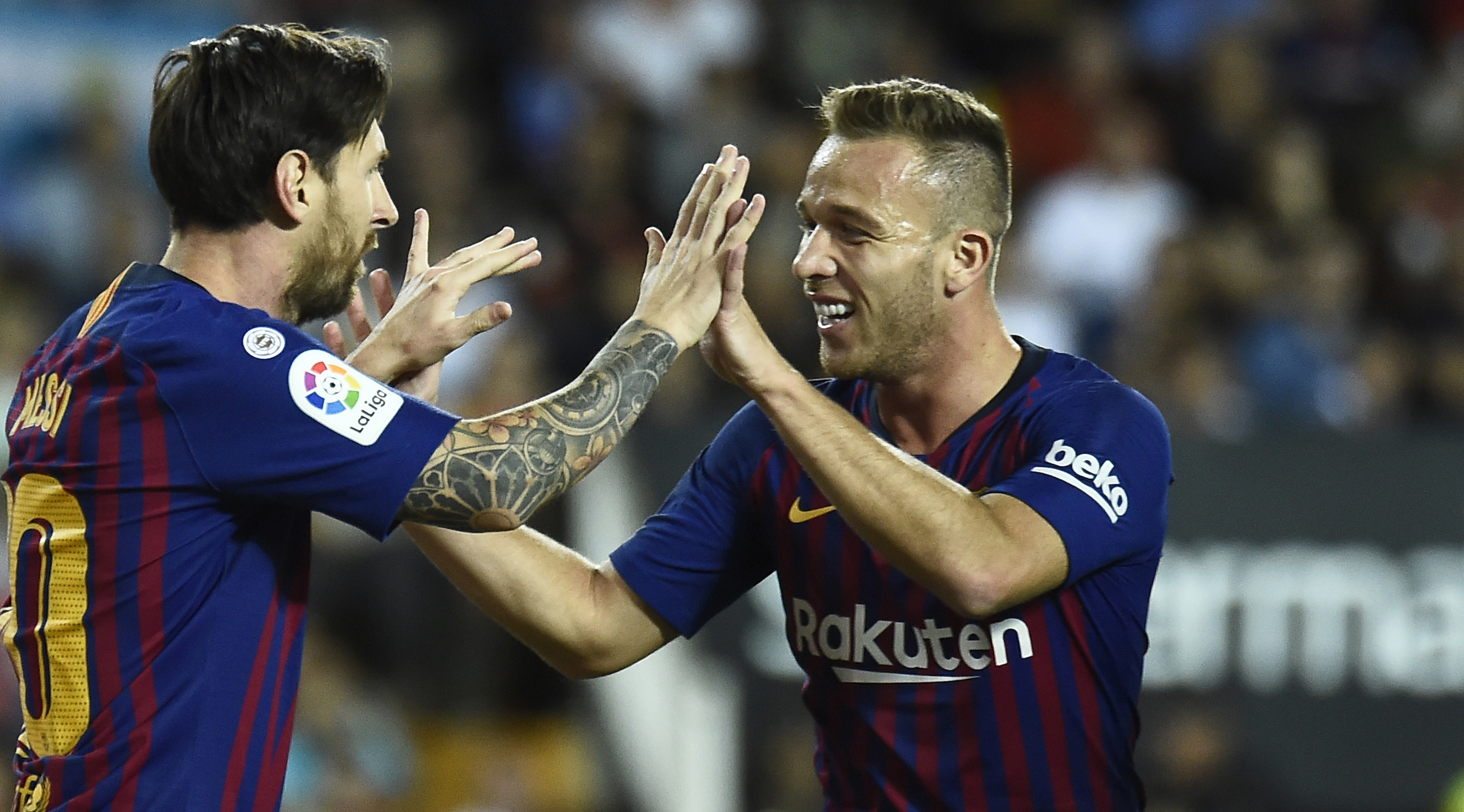 Barcelona's Argentinian forward Lionel Messi celebrates a goal with Barcelona's Brazilian midfielder Arthur during the Spanish league football match between Valencia CF and FC Barcelona at the Mestalla stadium in Valencia on October 7, 2018. (Photo by JOSE JORDAN / AFP) (Photo credit should read JOSE JORDAN/AFP/Getty Images)