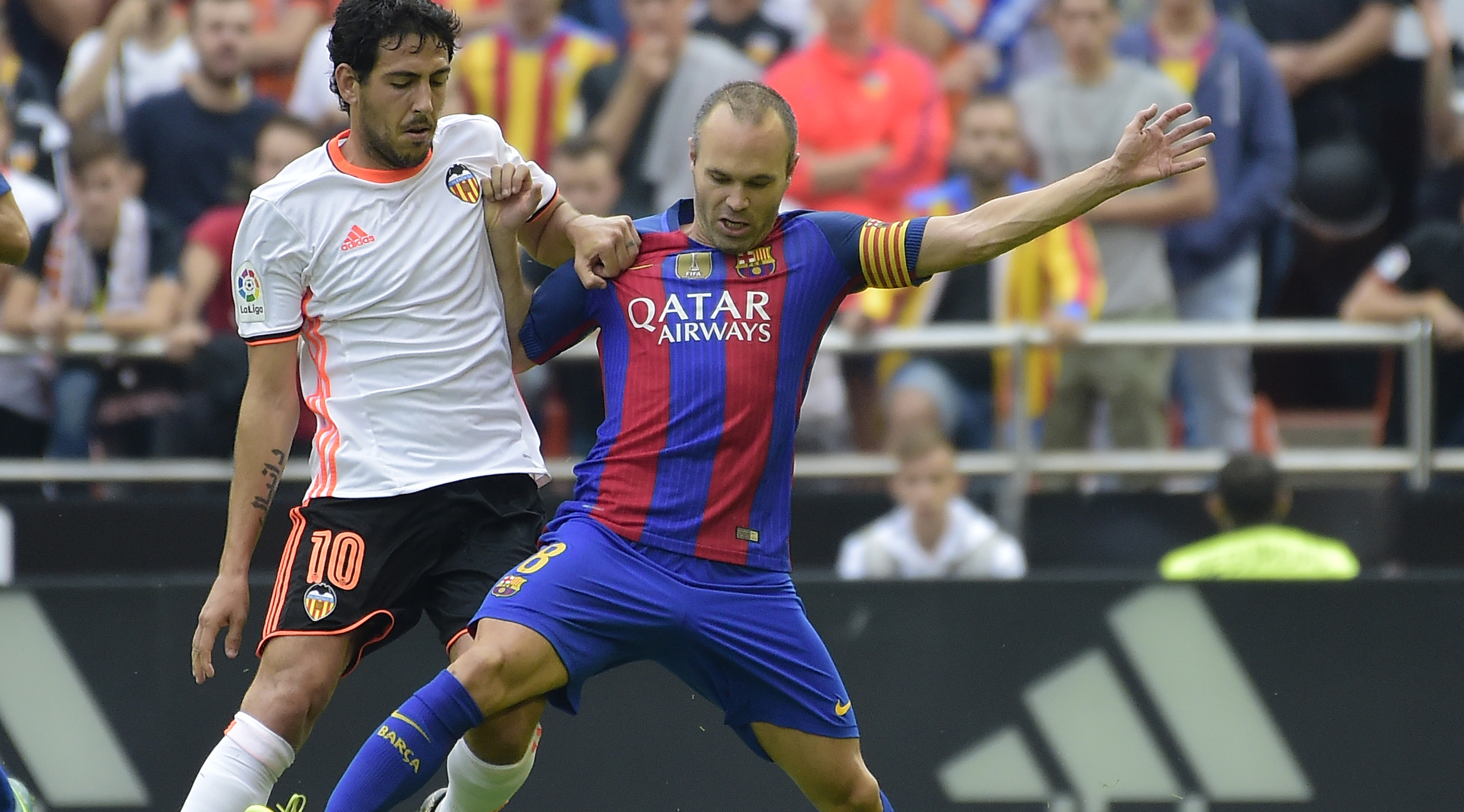 Valencia's midfielder Dani Parejo (L) vies with Barcelona's midfielder Andres Iniesta during the Spanish league football match between Valencia CF and FC Barcelona at the Mestalla stadium in Valencia on October 22, 2016. / AFP / JOSE JORDAN (Photo credit should read JOSE JORDAN/AFP/Getty Images)