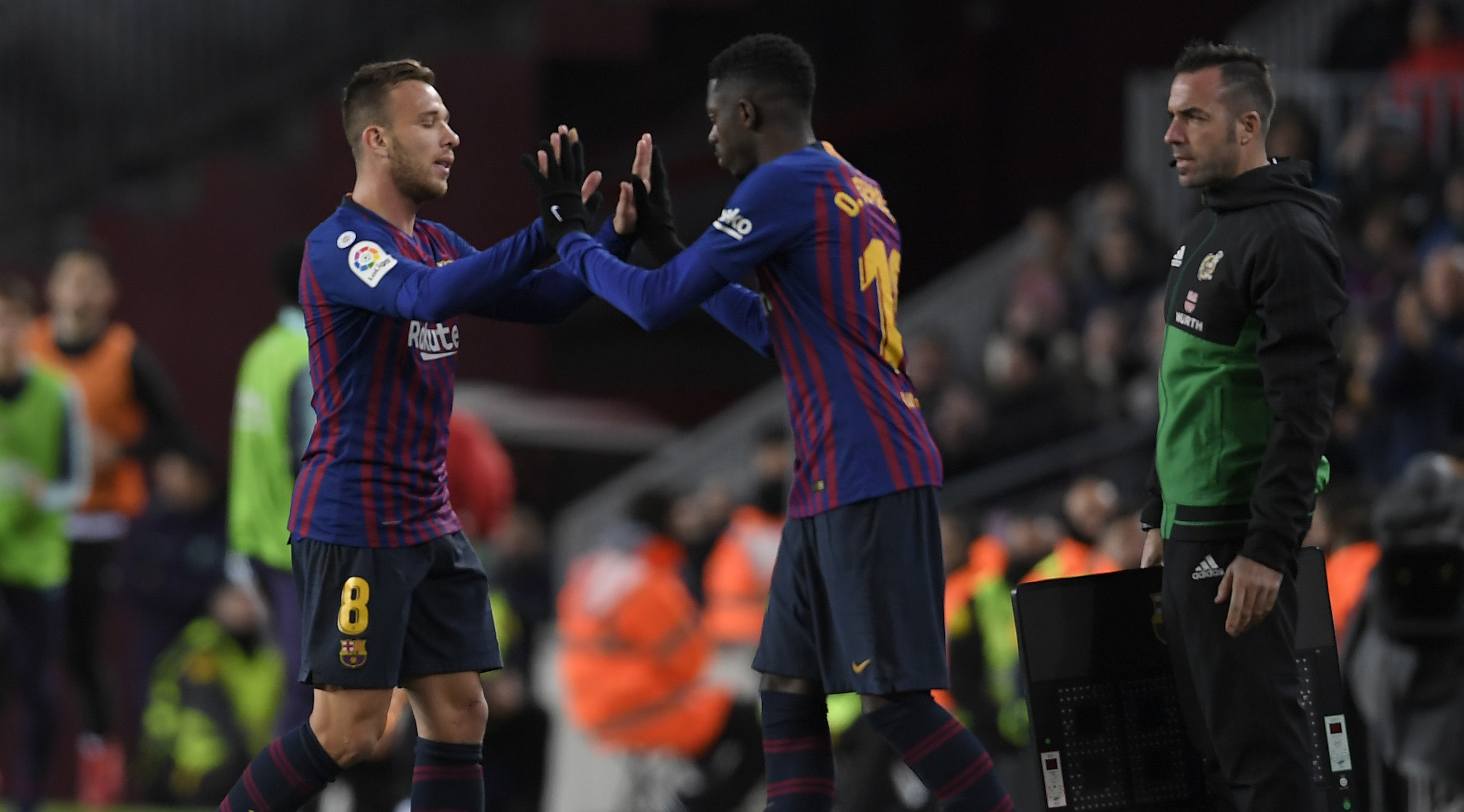 Barcelona's Brazilian midfielder Arthur (L) greets Barcelona's French forward Ousmane Dembele as he leaves the pitch during the Spanish League football match between FC Barcelona and SD Eibar at the Camp Nou stadium in Barcelona on January 13, 2019. (Photo by LLUIS GENE / AFP) (Photo credit should read LLUIS GENE/AFP/Getty Images)