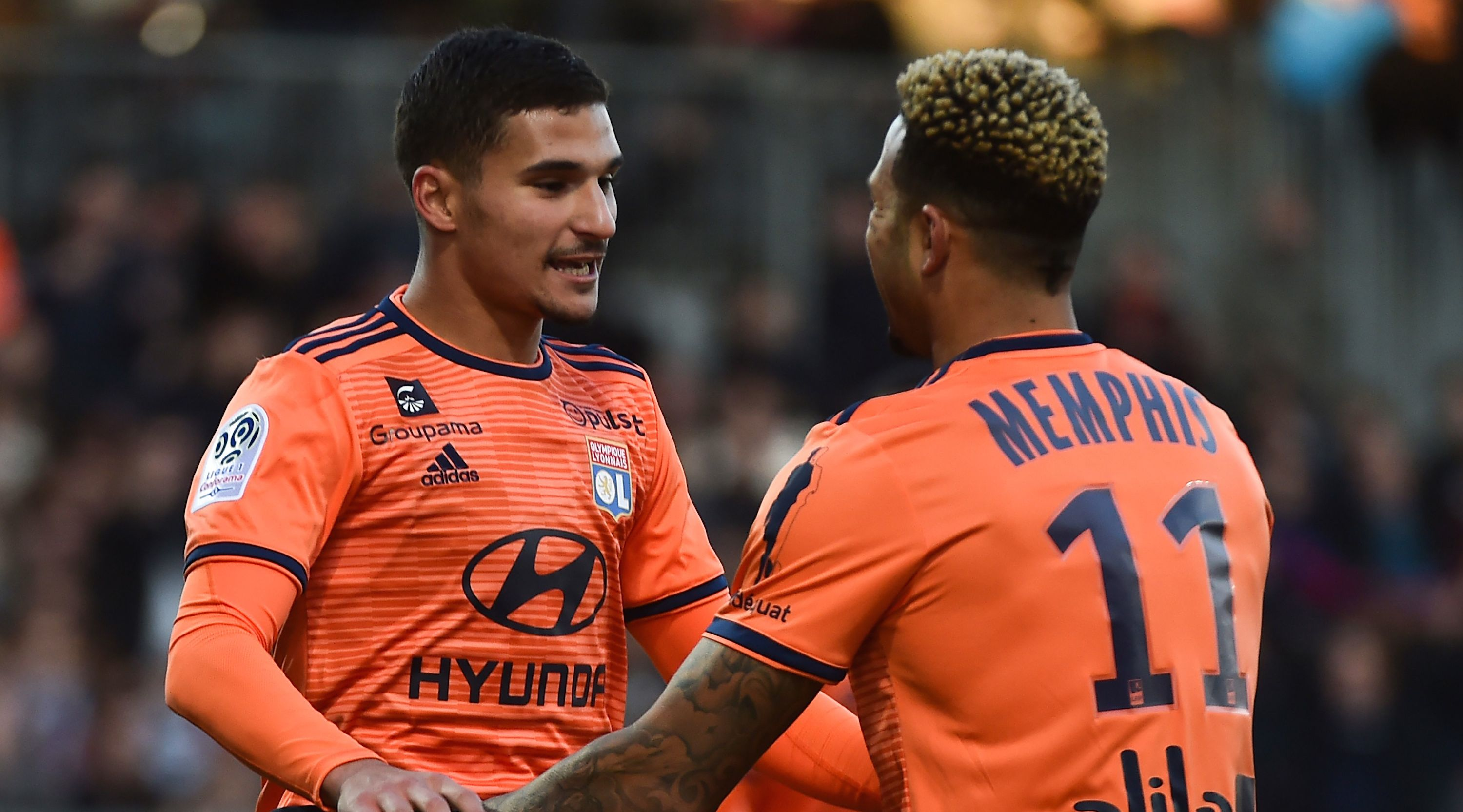Lyon's French midfielder Houssem Aouar (L) celebrates with Lyon's Dutch forward Memphis Depay (R) after scoring a goal during the French L1 football match between Angers (SCO) and Lyon (OL), on October 27, 2018, at the Raymond-Kopa Stadium, in Angers, northwestern France. (Photo by JEAN-FRANCOIS MONIER / AFP) (Photo credit should read JEAN-FRANCOIS MONIER/AFP/Getty Images)