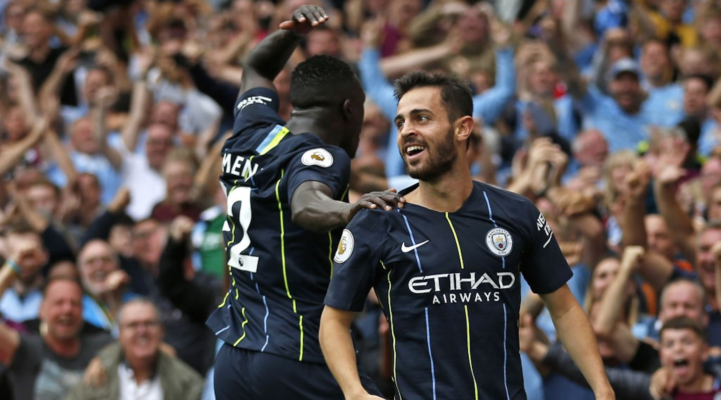 Manchester City's Portuguese midfielder Bernardo Silva (R) celebrates with Manchester City's French defender Benjamin Mendy after scoring their second goal during the English Premier League football match between Arsenal and Manchester City at the Emirates Stadium in London on August 12, 2018. (Photo by Ian KINGTON / IKIMAGES / AFP) /