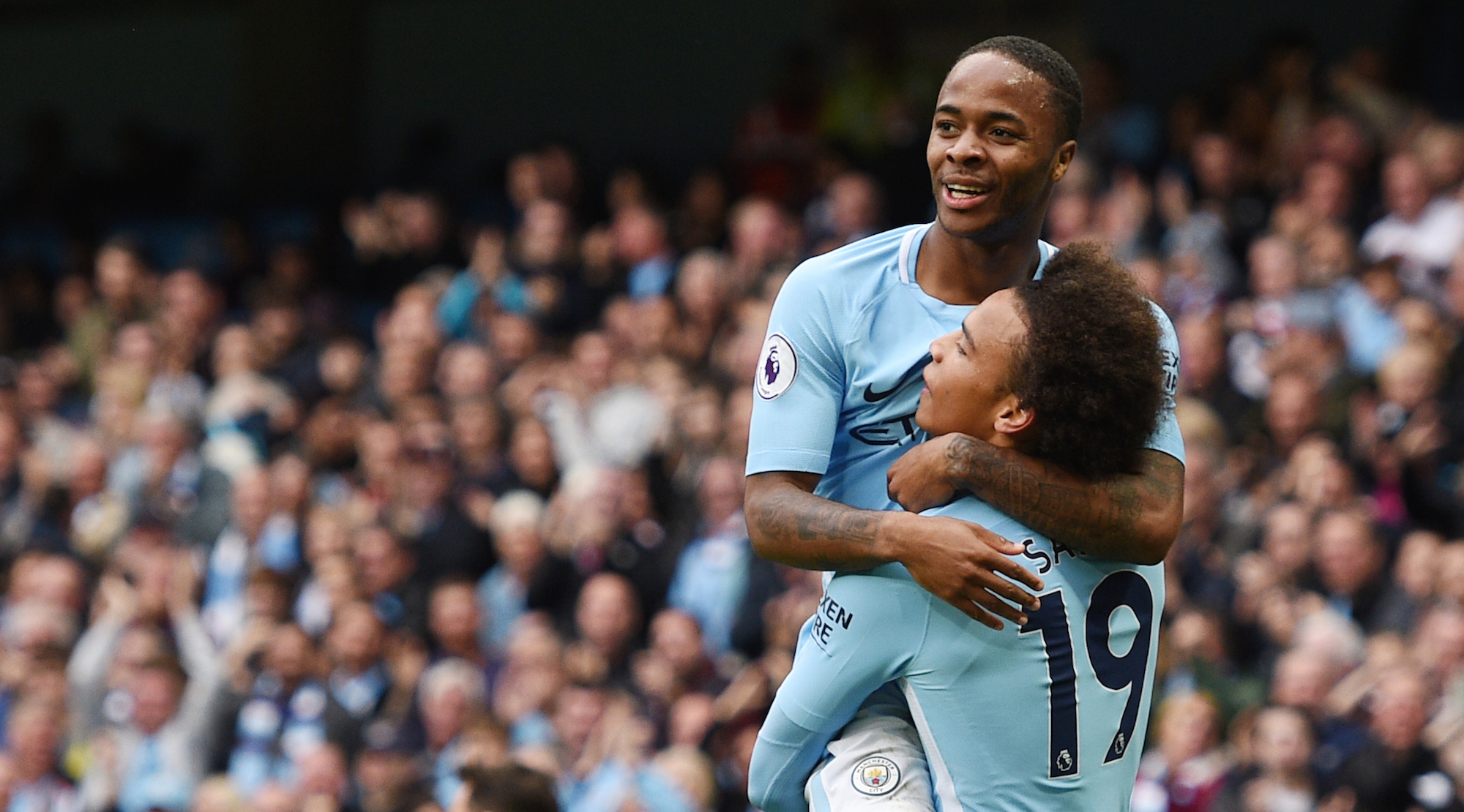 Manchester City's English midfielder Raheem Sterling (L) celebrates after scoring with Manchester City's German midfielder Leroy Sane during the English Premier League football match between Manchester City and Crystal Palace at the Etihad Stadium in Manchester, north west England, on September 23, 2017. / AFP PHOTO / Oli SCARFF / RESTRICTED TO EDITORIAL USE. No use with unauthorized audio, video, data, fixture lists, club/league logos or 'live' services. Online in-match use limited to 75 images, no video emulation. No use in betting, games or single club/league/player publications. / (Photo credit should read OLI SCARFF/AFP/Getty Images)