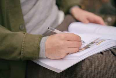 anonymous man doing homework in workbook in park