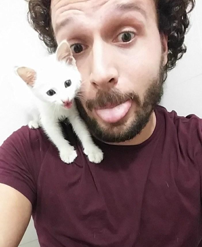 男性といっしょにベロを出す子猫