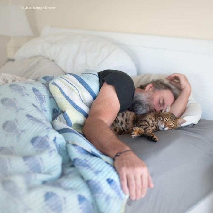 一緒に眠る猫と男性