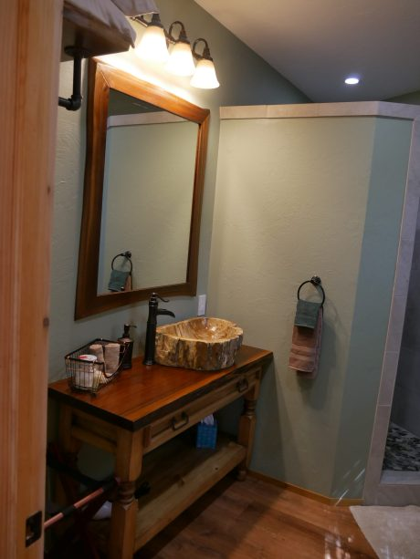 The bathroom features a petrified wood sink on a locally sourced black walnut vanity top. There is also a luggage rack and place to hang your clothes.