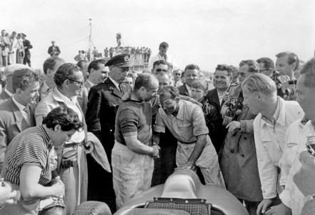 Großer Preis von Holland in Zandvoort am 19. Juni 1955. Sieger Juan Manuel Fangio beglückwünscht Stirling Moss, der Zweiter wurde. Dutch Grand Prix in Zandvoort on 19 June 1955. Winner Juan Manuel Fangio congratulates Stirling Moss, who finished second. Both drivers were in Mercedes-Benz Formula One racing cars W 196 R with free-standing wheels.