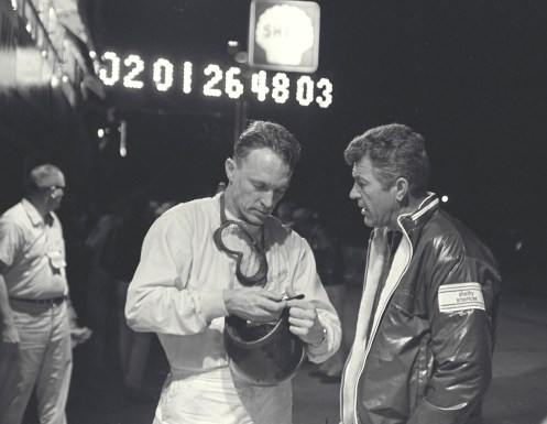 Sebring 12 Hour Race, Sebring, FL, 1966. Dan Gurney (left) and Carroll Shelby (right) talk during a night pit stop of the Sebring 12 Hour Race.