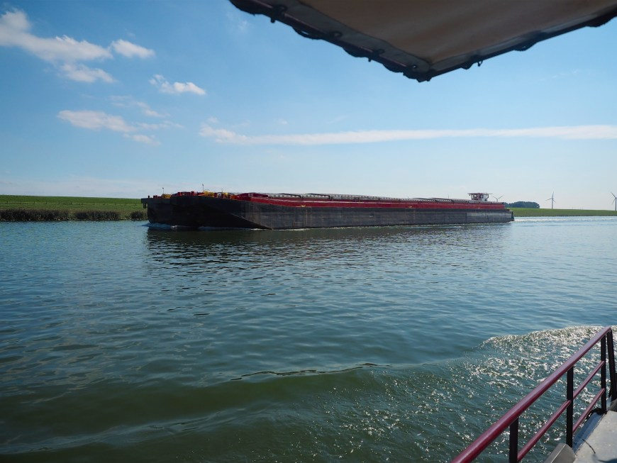 Two large unpowered barges being pushed by a pusher.