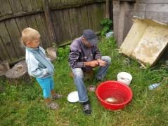 Nasar passt auf, dass Opa alles richtig macht beim Fische-Ausnehmen