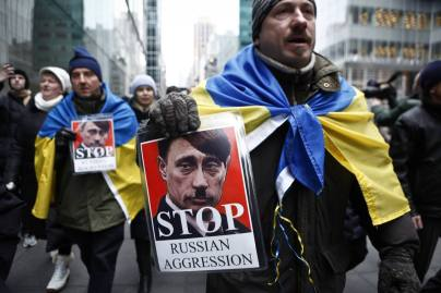 A man holds a sign in a protest against Russian military intervention in the Crimea region of Ukraine on March 2, 2014 in New York City.