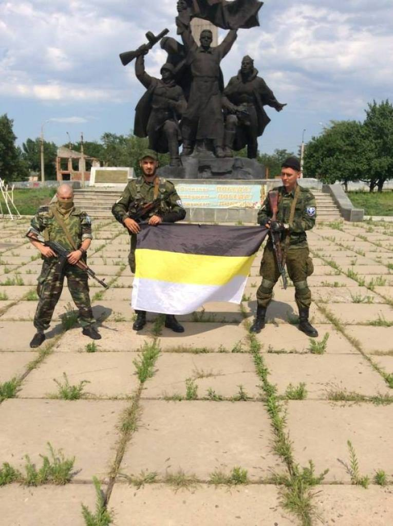Three members hold the Russian imperial flag, used by far-right groups