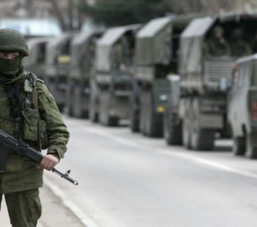 "Unmarked trucks with Putin's so-called ""little green men"" - heavily-armed Russian cadres military troops hiding their identities and without insignia during the invasion into the Ukrainian peninsula of Crimea in February 2014."